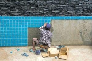 man installing pool tiles
